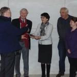 Burgemeester Loes van Ruijven neemt het boekje in ontvangst uit handen van auteur/vrijwilliger Hans Tevel